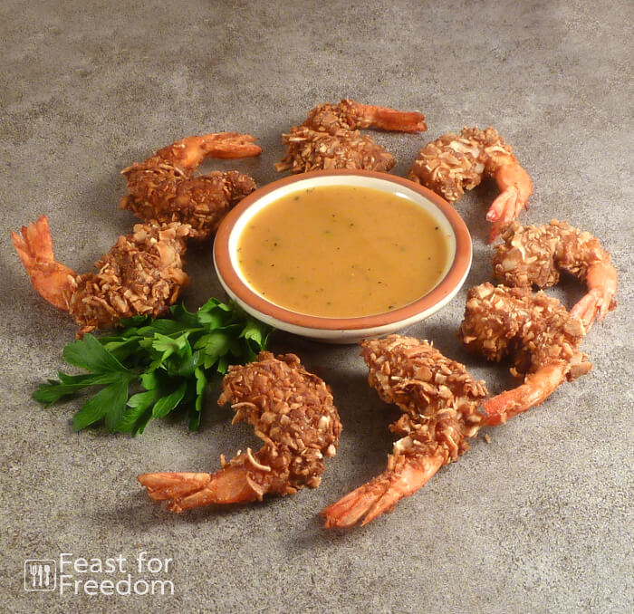 Coconut shrimp on a platter with honey mustard sauce in a small bowl