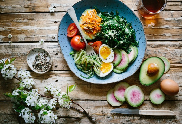 Plate of food on a rustic table with eggs, veggies and salad