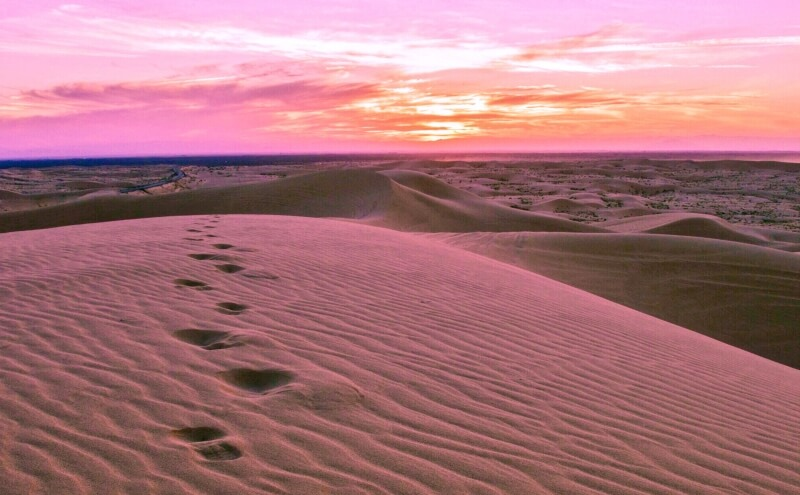 Footprints in sand against a pink sunset