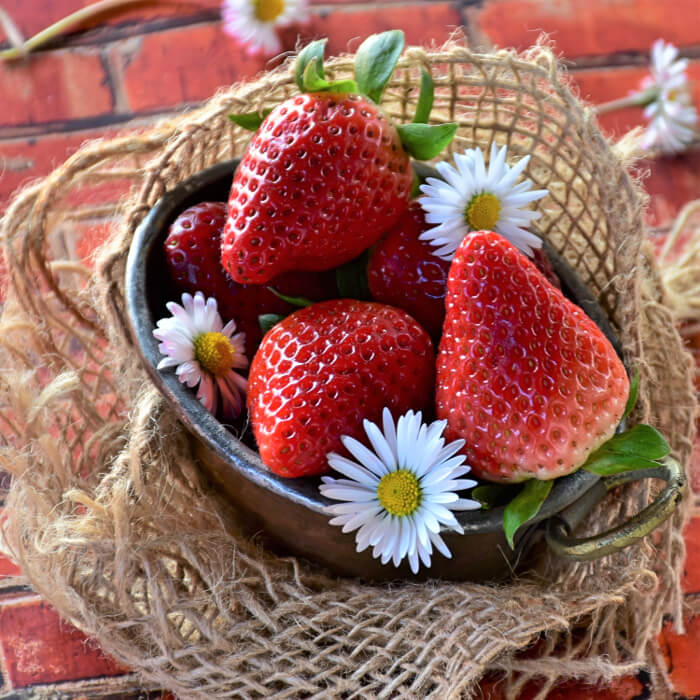 Fresh strawberries in a small tin bucket