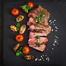 Sliced steak on a black stone tablet