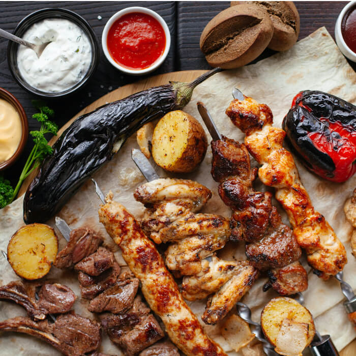 Shish kabobs on a platter with sauces