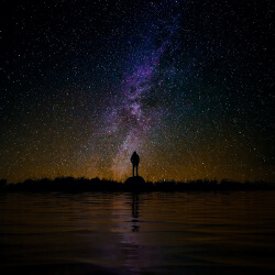 Woman standing on a rock looking out to the night sky