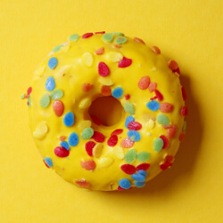 Bright yellow glazed donut with multicolored sprinkles