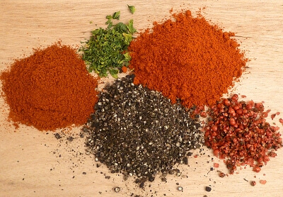 The spices for all purpose seasoning in little piles on a cutting board