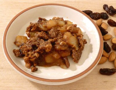Apple Crisp on a plate with toasted almonds using panela sugar and raisins