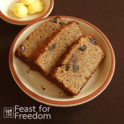Slices of banana bread with raisins on a plate, with a small dish of butter next to it