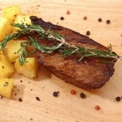 Cut of marinated beef steak with rosemary and cubed potatoes on a cutting board