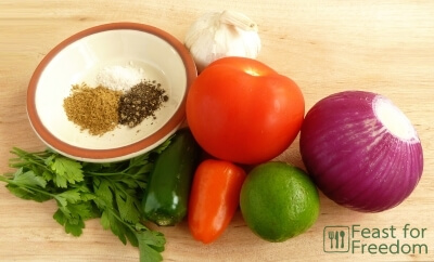 Fresh ingredients to make salsa - tomatoes, jalapenos, lime, onion, garlic, parsley, spices