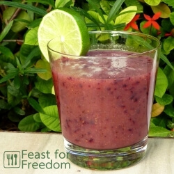 Blueberry and kiwi smoothie in a glass on a table next to a green bush, garnished with lime