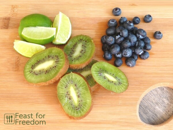 Sliced limes and kiwis and a small pile of blueberries on a bamboo cutting board