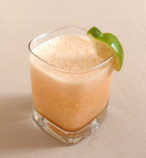 Cantaloupe smoothie in a glass with a lime garnish