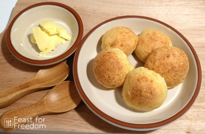 Cheese buns on a plate next to a small dish of butter
