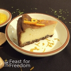 New York style baked cheesecake on a plate, next to a small bowl of Mango Sauce, sprinkled with orange and lime zest