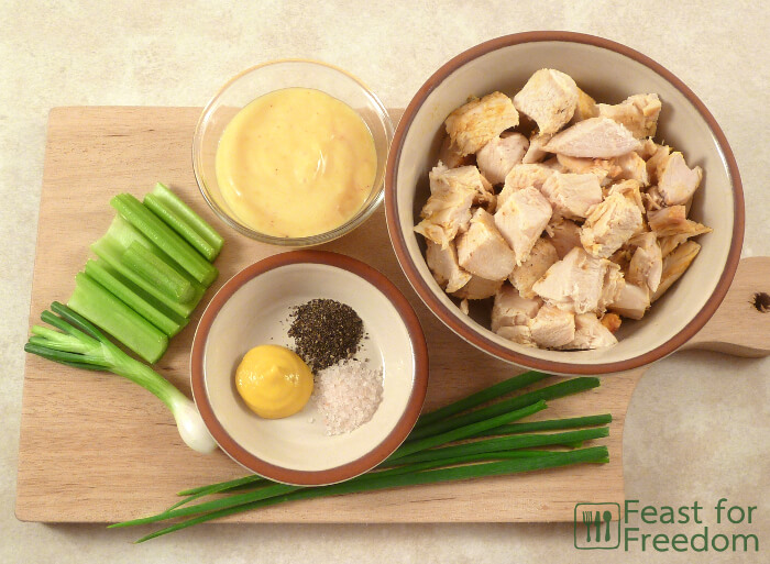 Ingredients needed to make chicken salad on a cutting board - chicken, celery, green onions, mayonnaise, mustard, salt and pepper