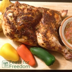 Baked chicken basted with fresh salsa on a wooden cutting board