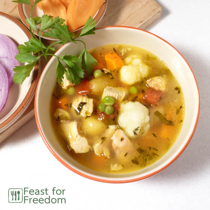 Chicken soup in a bowl next to fresh carrots and onions, and garnished with parsley