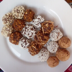 No bake chocolate cookie balls on a plate with various coatings