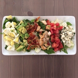 Fresh Cobb Salad on a rectangle plate, layed out in small rows