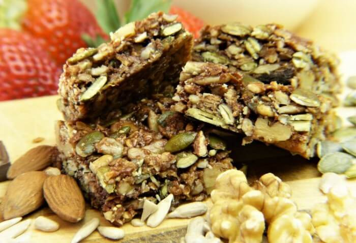 Stack of homemade coconut and nut treats with almonds and pumpkin seeds
