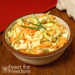 Creamy coleslaw in a bowl with a green onion garnish
