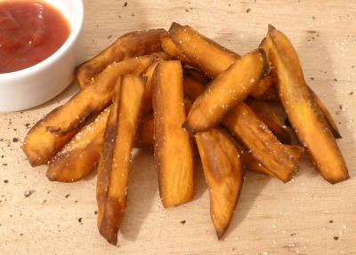 Sweet potato fries on a board, sprinkled with seasoning, next to a bowl of ketchup