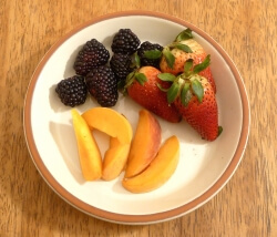 Cut up mixed fruit on a plate