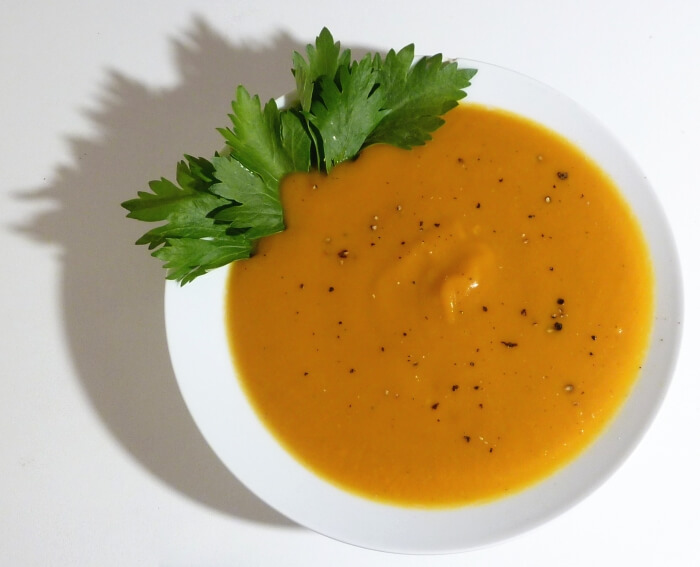 Ginger squash soup in a bowl with a sprig of parsley and fresh ground pepper.