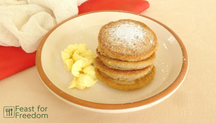 Stack of gluten free pancakes with butter and powdered sugar