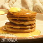 Grain free pancakes on a plate with butter and syrup