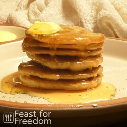 Stack of grain free and gluten free pancakes with butter and pancake syrup