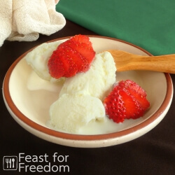 Vanilla ice cream in a bowl topped with fresh strawberries