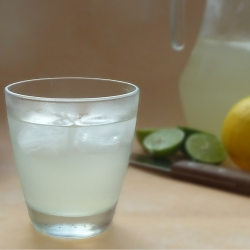 Lemonade in a glass next to lemons and limes