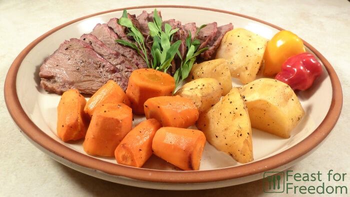 Roast beef on a plate with potatoes and carrots