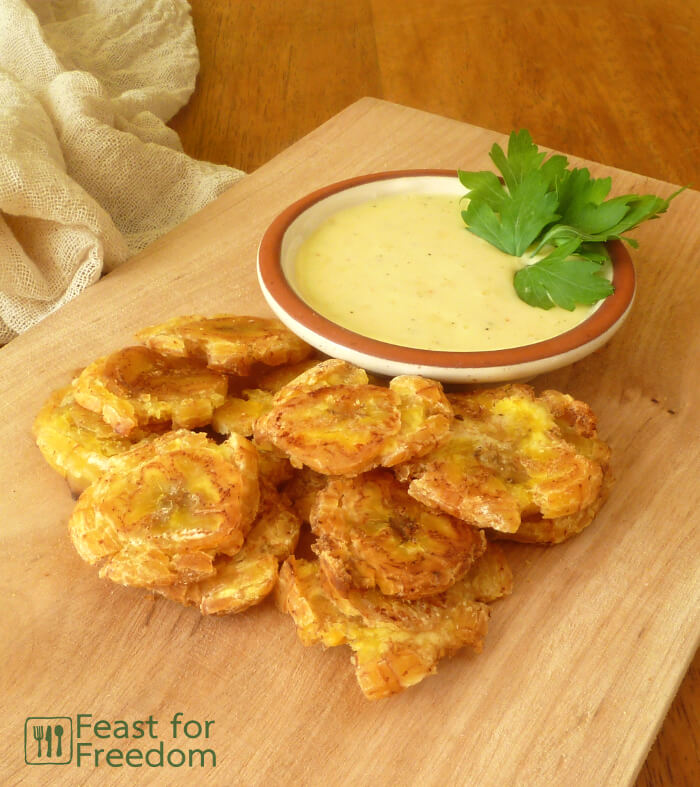 Fried Patacones on a wooden platter with a dish of garlic and lime mayo dip