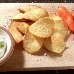 Potato chips on a wooden board, sprinkled with coarse salt and freshly ground pepper, next to a bowl of chip dip