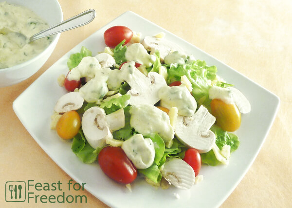 Salad on a plate topped with ranch dressing
