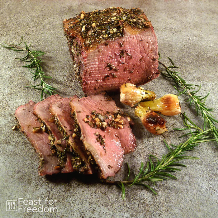 Sliced roast beef with pearl onions and rosemary sprigs