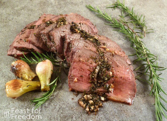 Sliced roast beef with fresh rosemary and roasted onions