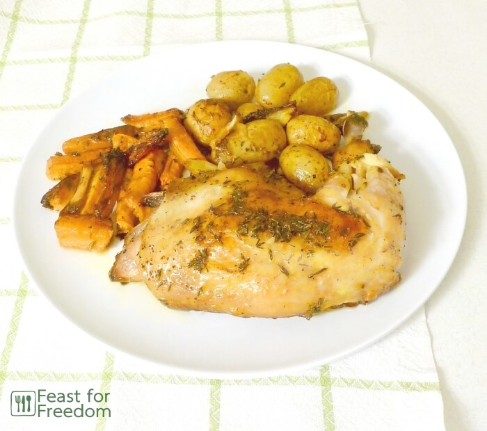Roast chicken with roasted carrots and potatoes on a plate