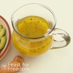 Shake and serve simple salad dressing in a glass jar next to a veggie plate