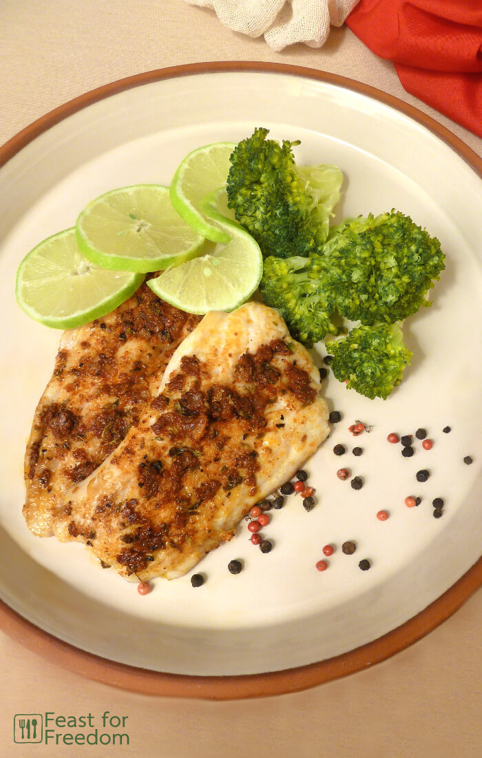 Pan fried fish with a savory spice rub with steamed broccoli and limes