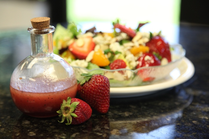 Strawberry salad dressing in bubble bottle next to a fruit salad
