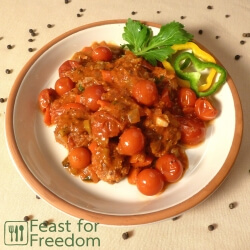 Meatballs with cherry tomato sauce on a plate garnished with sweet peppers and celery leaves
