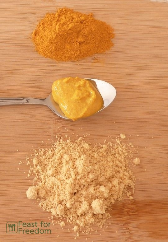 Yellow mustard on a spoon next to small piles of turmeric and mustard powder